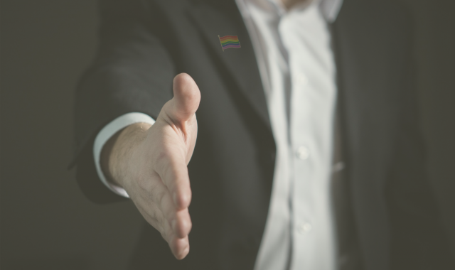 lgbt flag on suit; man reaching out his hand to shake