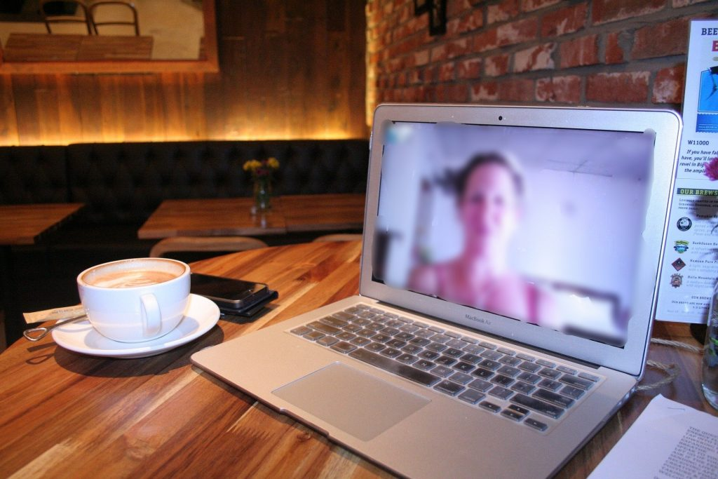 virtual meeting with woman on a computer screen next to a latte